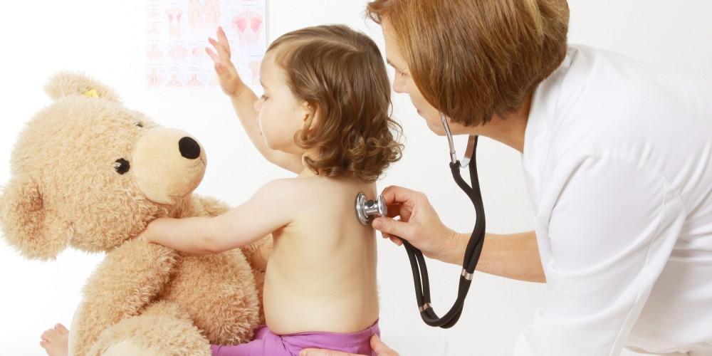 Ärztin hört Kind mit einem Stethoskop ab