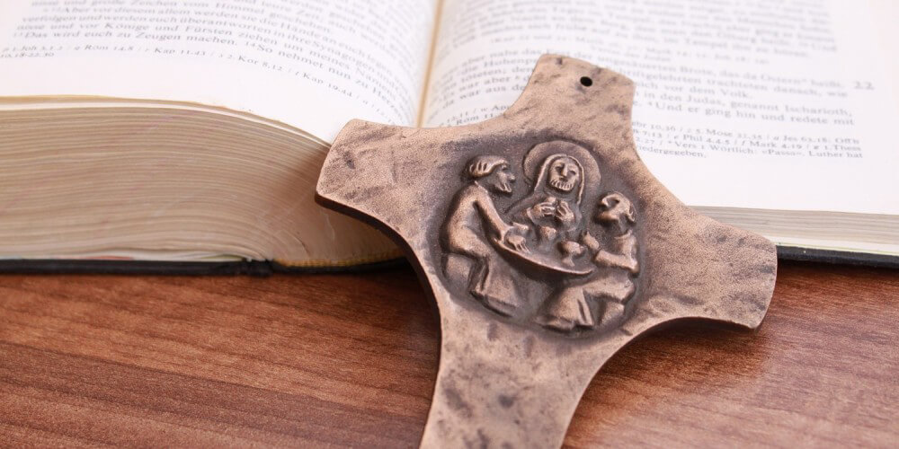 Aufgeschlagene Bibel, davor Kreuz aus Bronze