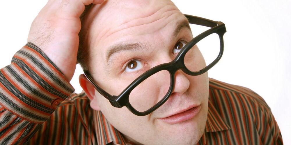Mann mit Glatze und schiefsitzender, großer Hornbrille kratzt sich am Kopf, grübelt