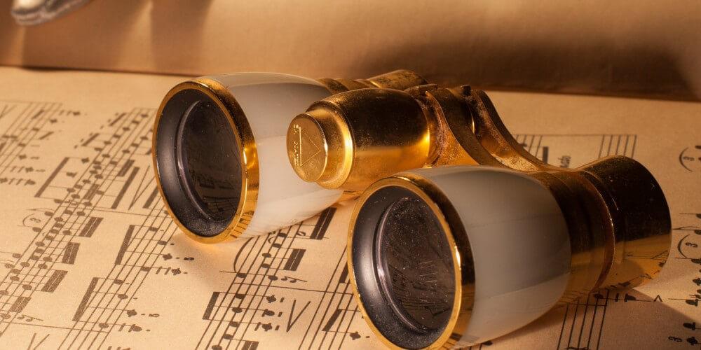 Goldenes Opernglas neben feinem Handschuh auf einem Notenheft