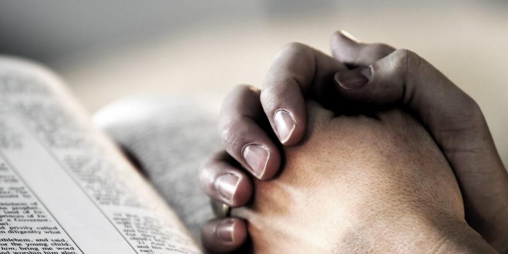 Gefaltete Hände auf einer Bibel