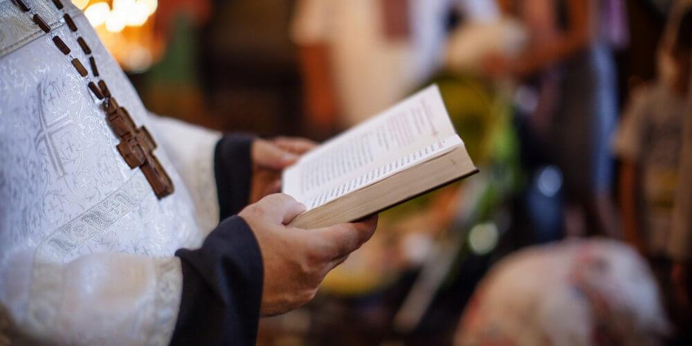 Ein Priester liest aus einer Bibel