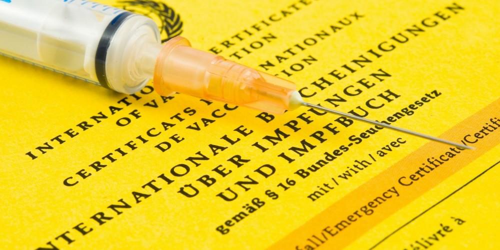 Spritze auf gelbem Impfausweis