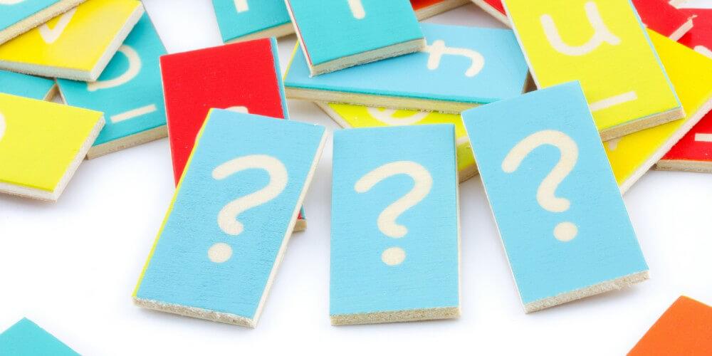 Bunte Holzplättchen, im Vordergrund drei blaue Plättchen mit Fragezeichen