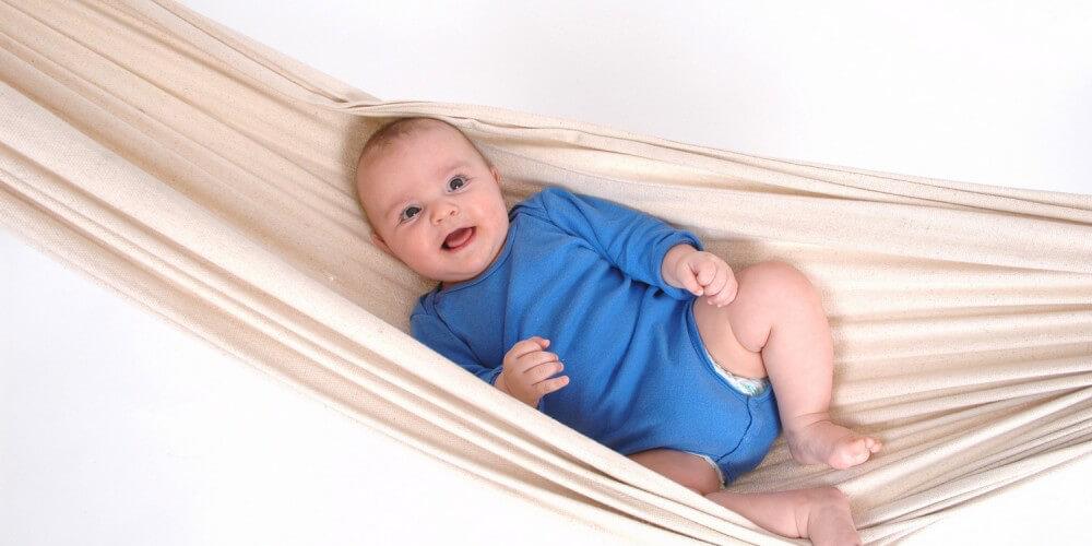 Baby in blauem Body liegt in einer Hängematte
