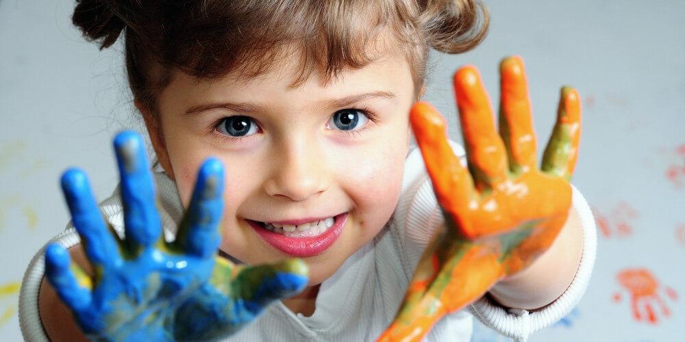 Glückliches Mädchen mit Fingerfarbe an den Händen