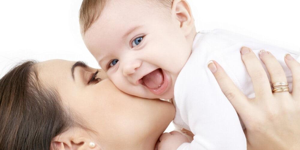 Eine Mutter hält ihr lachendes Baby hoch