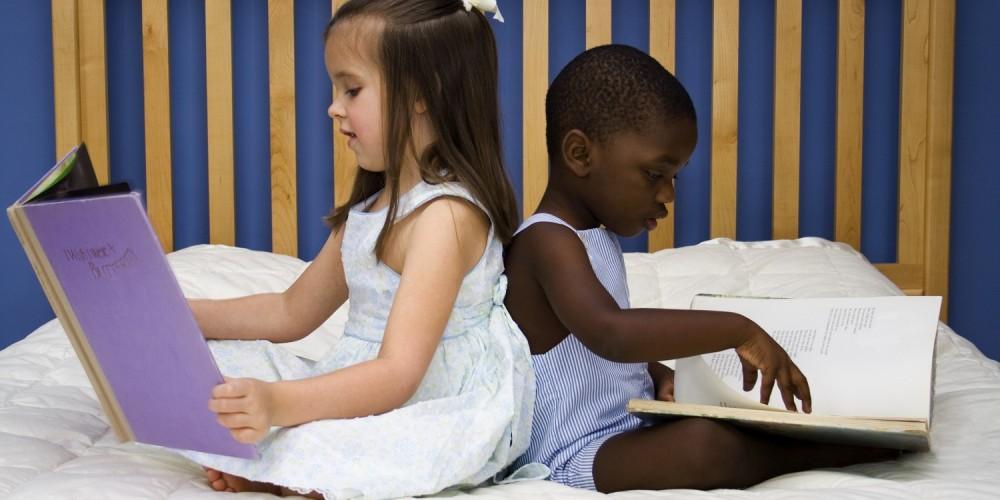 Zwei Kinder beim Bücherlesen im Bett