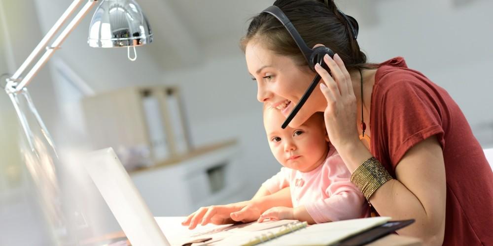 Frau mit Baby im Arm arbeitet am Computer