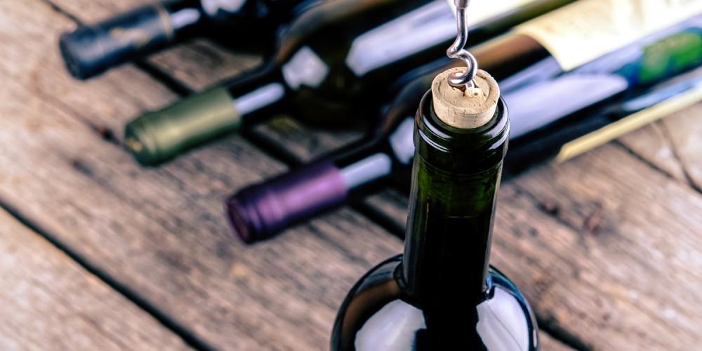 Weinflasche wird mit einem Korkenzieher geöffnet
