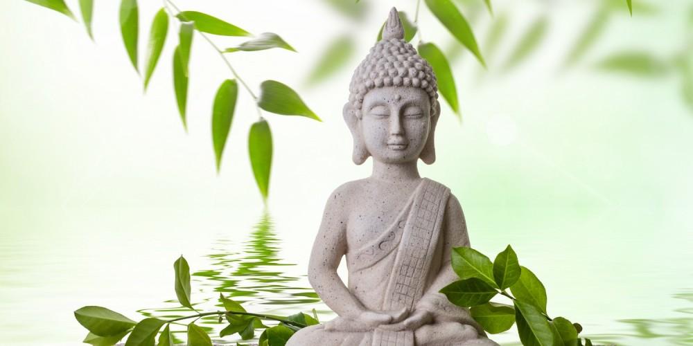 Buddhafigur neben Bambusblättern im Wasser