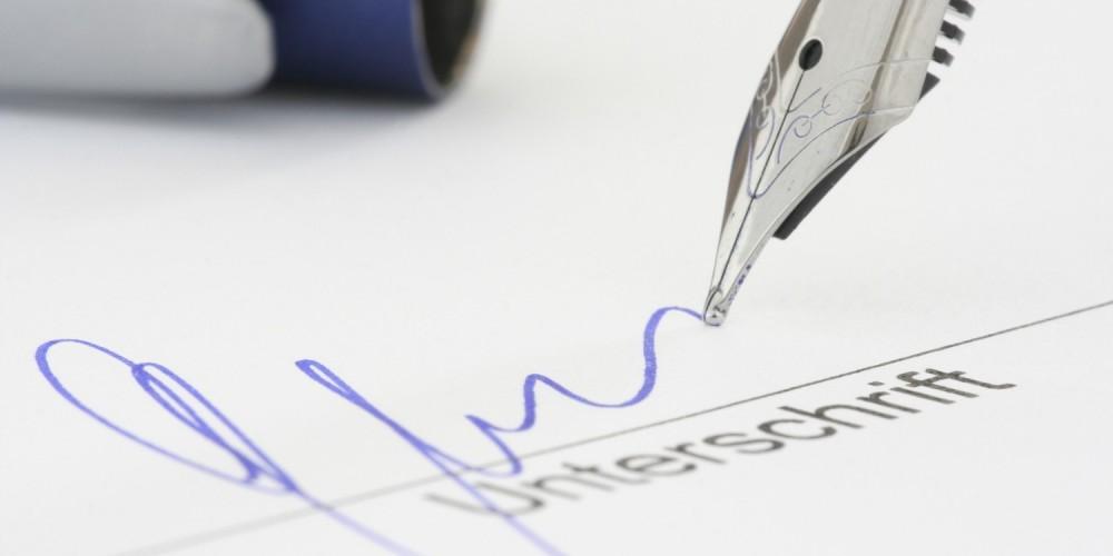 Füllfederhalter unterschreibt mit blauer Schrift auf weißem Papier
