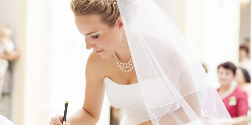 Hochzeitsbraut bei der Unterschrift im Standesamt