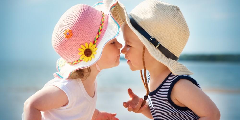 Junge und Mädchen mit Sonnenhut am Strand