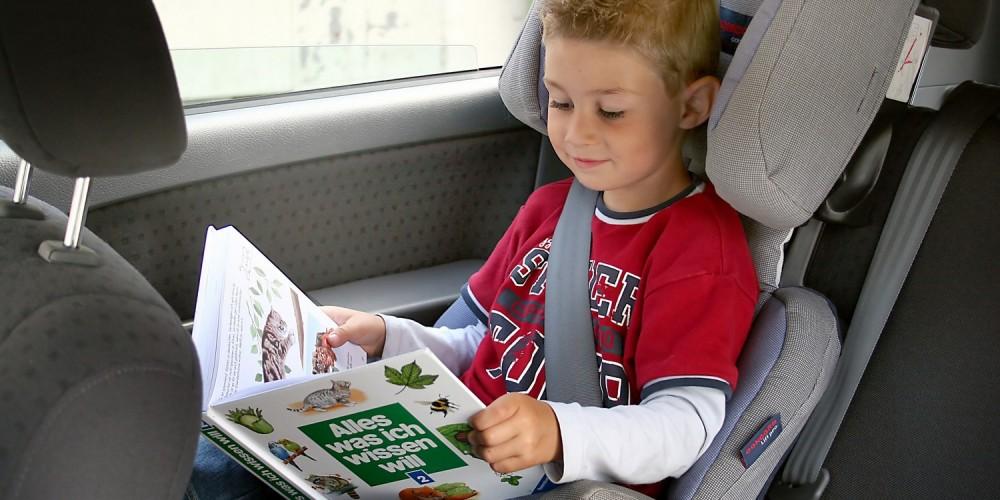 Junge blättert während der Autofahrt in einem Buch