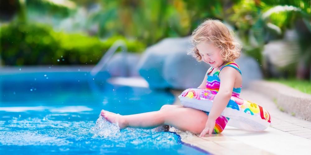Kleines Mädchen sitzt mit Schwimmreifen am Pool