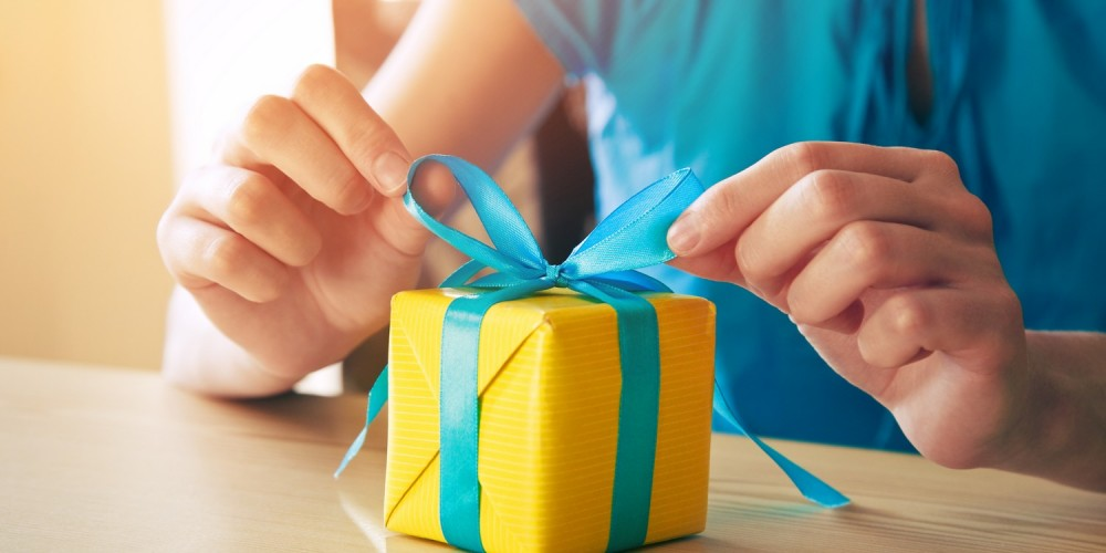 Frau bindet eine blaue Schleife an eine kleine gelbe Geschenkbox