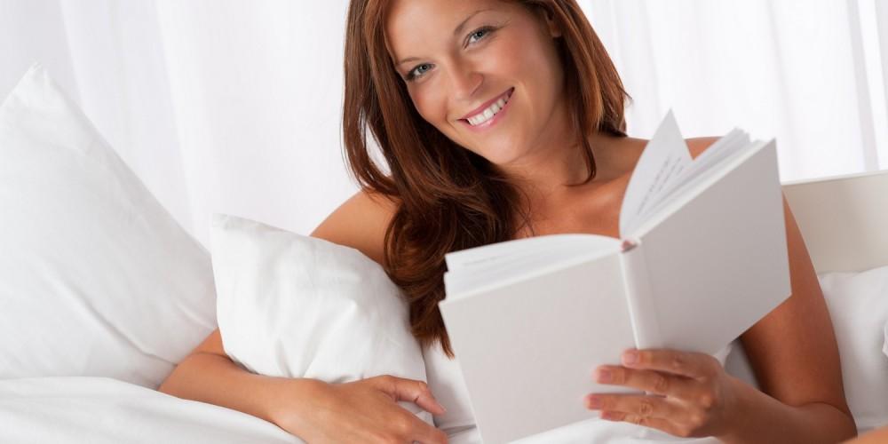 Frau liegt im Bett und liest in einem Buch