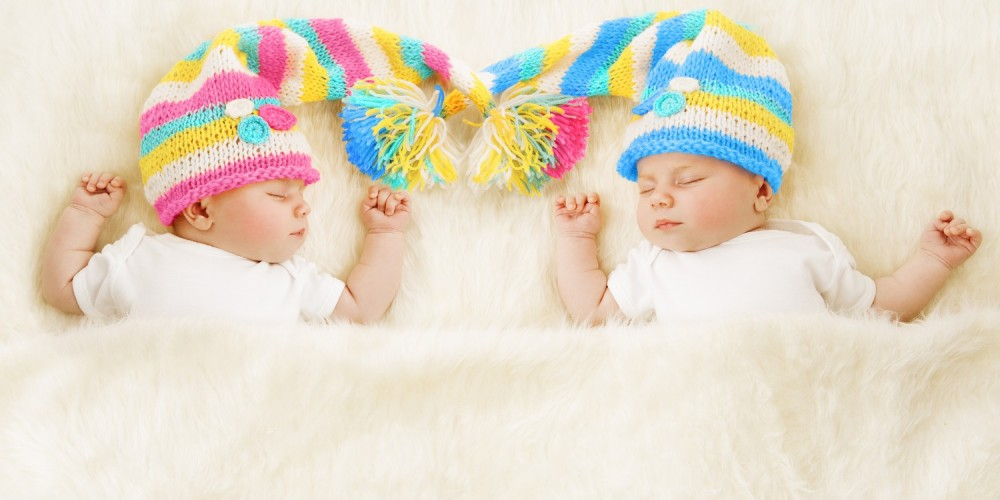 Zwillinge mit bunten Zipfelmützen auf dem Kopf