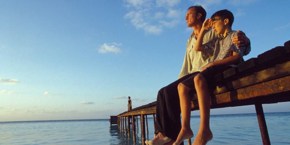 Vater und Sohn sitzen auf Bootssteg am Meer, schauen in den Sonnenuntergang, blauer Himmel