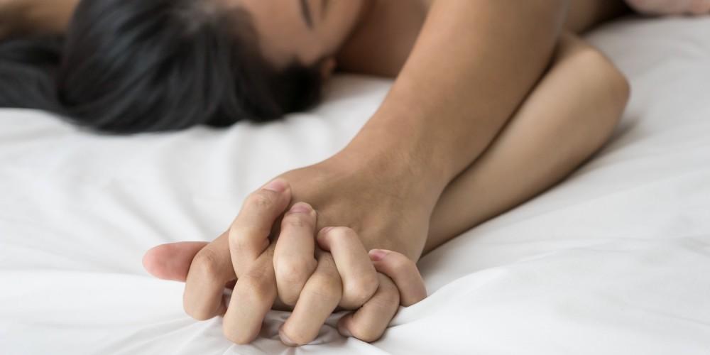 Paar hält sich die Hände beim Orgasmus