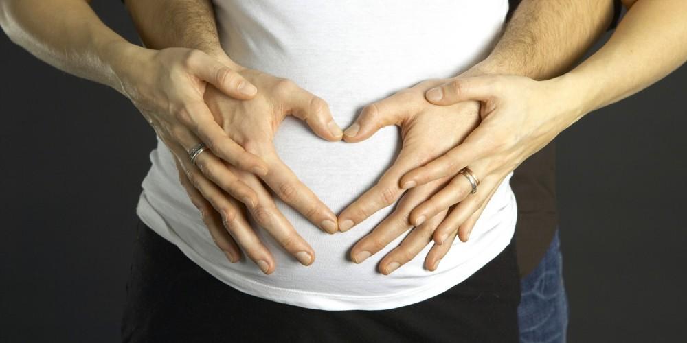 Paar hält seine Hände auf dem Babybauch