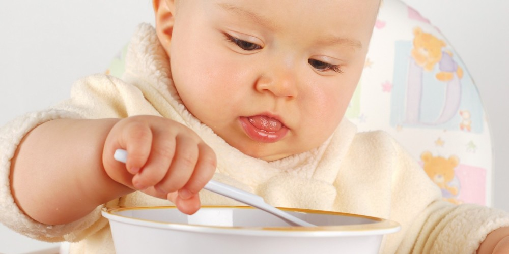 Baby im gelben Strampler isst mit Plastiklöffel aus Plastikschale, die Zunge halb herausgesteckt