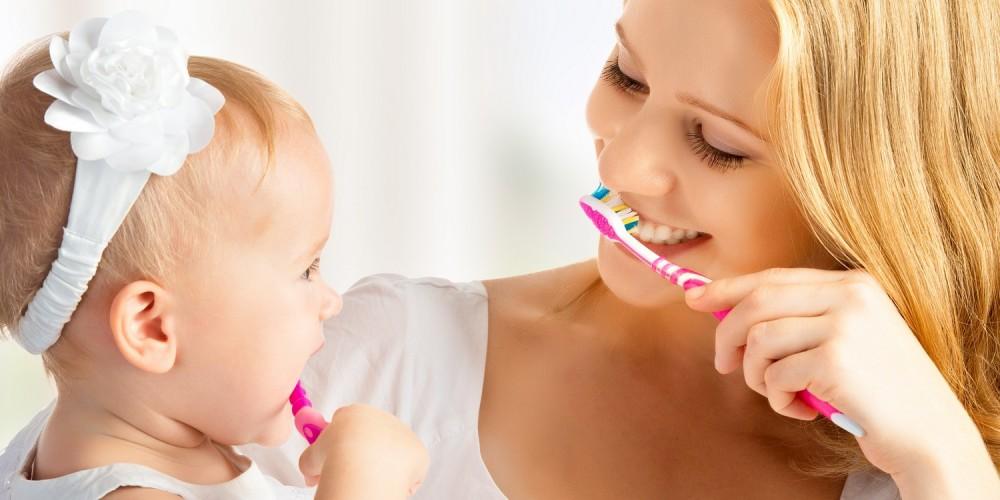 Junge Mutter und Tochter (Baby) beim Zähneputzen