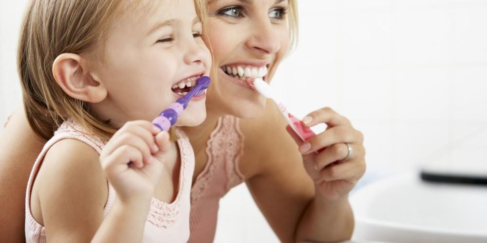 Mutter mit Tochter beim Zähneputzen