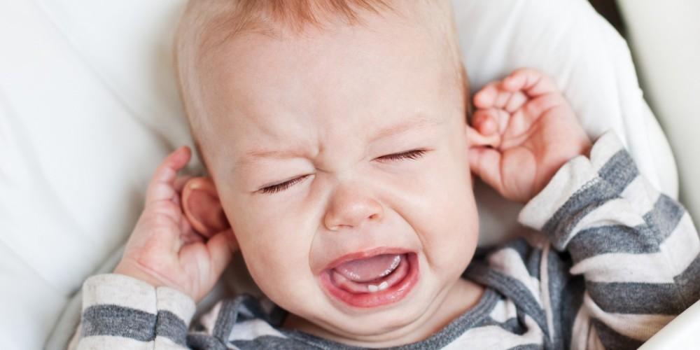 Weinendes Kleinkind hält sich die Ohren