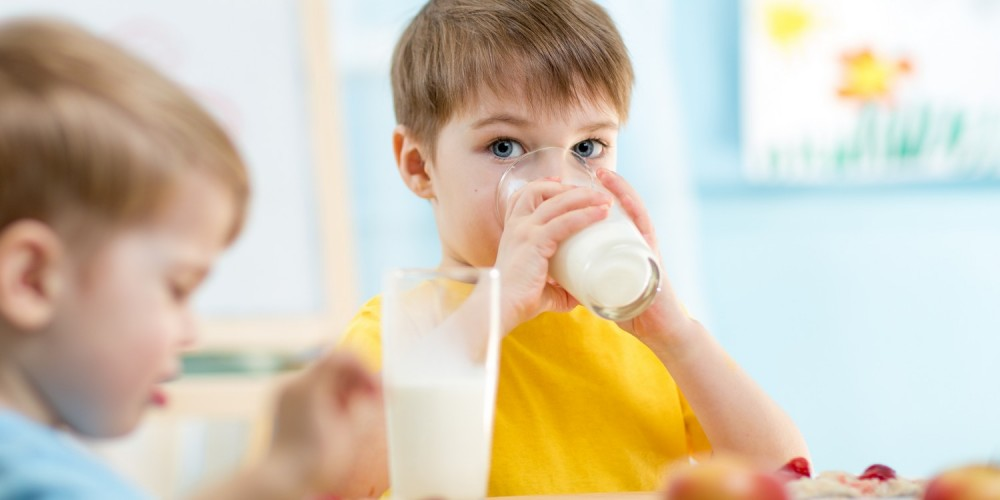 Kinder sitzen am Tisch und trinken Milch
