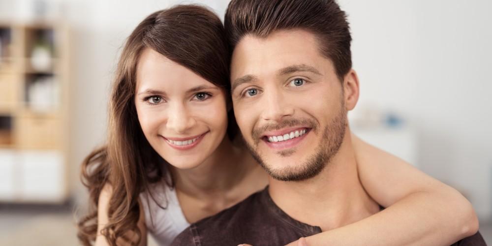 Portrait eines jungen glücklichen Paares in Wohnung, sie umarmt ihn von hinten