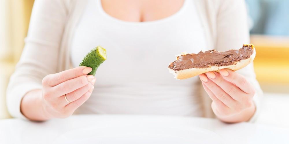 Frau isst Gewürzgurke und Schokoladenbrot