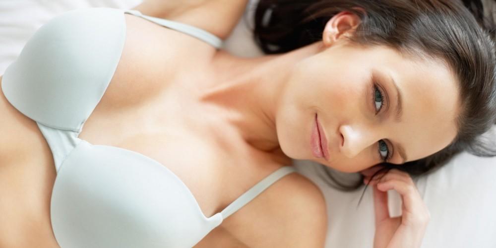 Frau liegt in Dessous auf dem Bett