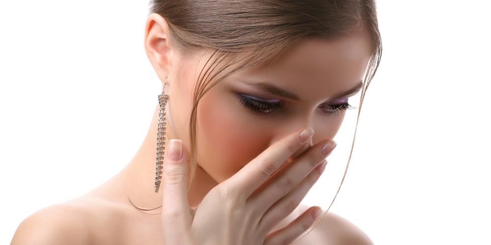 Frau fasst sich geekelt an die Nase