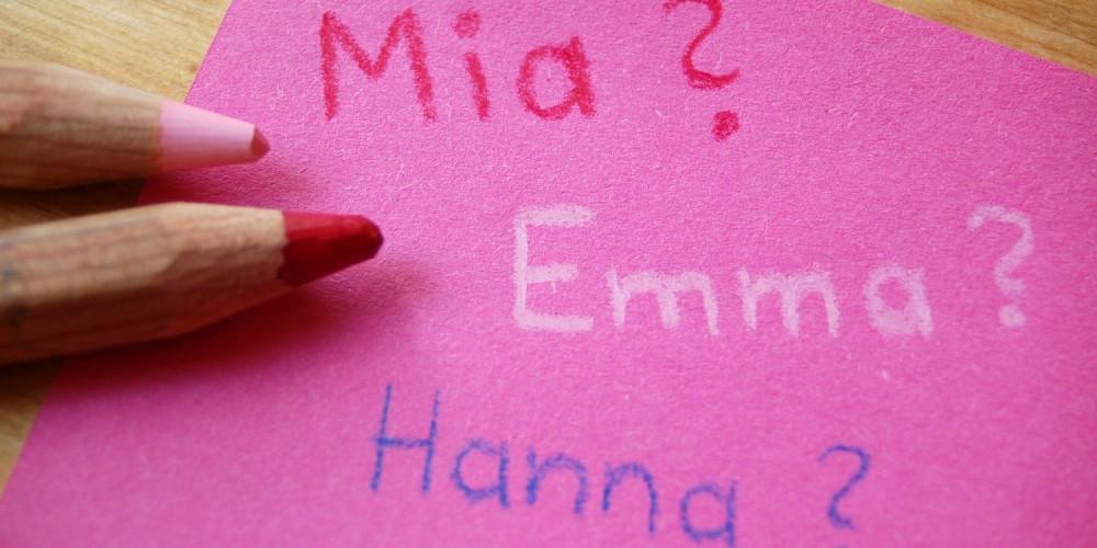 Pinker Zettel mit Mädchennamen neben Buntstiften