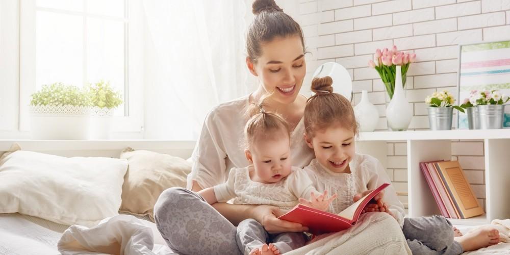Mutter liest ihren beiden Kindern ein Buch vor