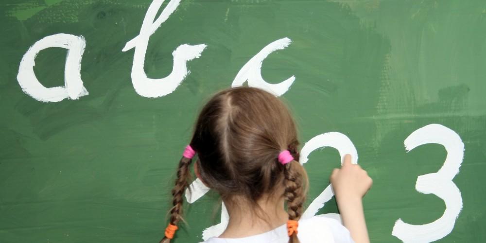 Rückansicht kleines Mädchen vor Tafel, abc, 123