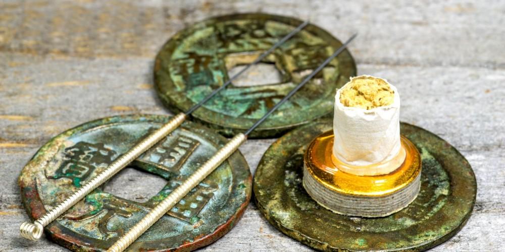 Zwei Akupunkturnadeln und Moxa auf antiken chinesischen Münzen