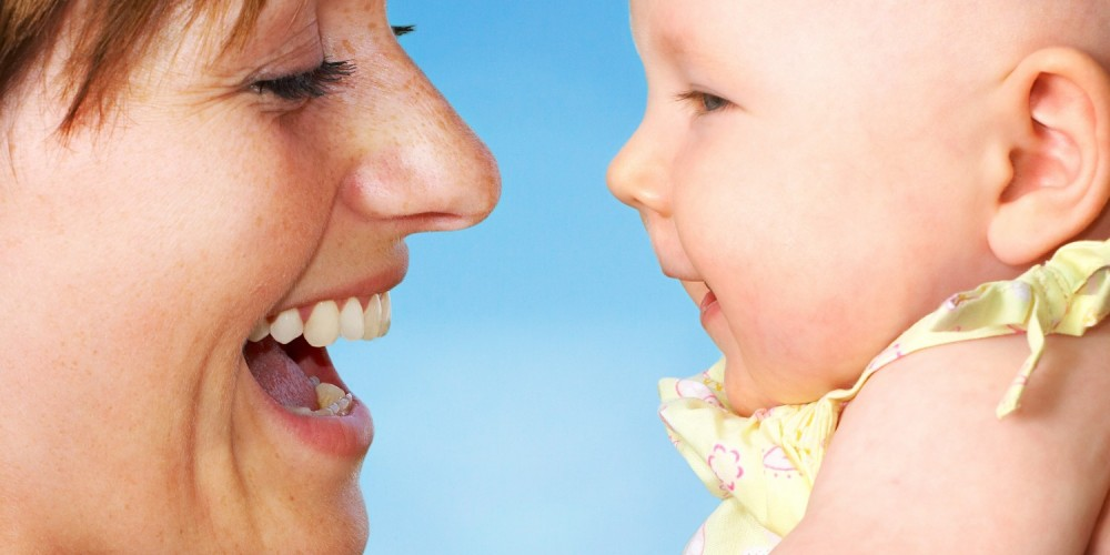 Lachende Mutter hält ihr Baby hoch