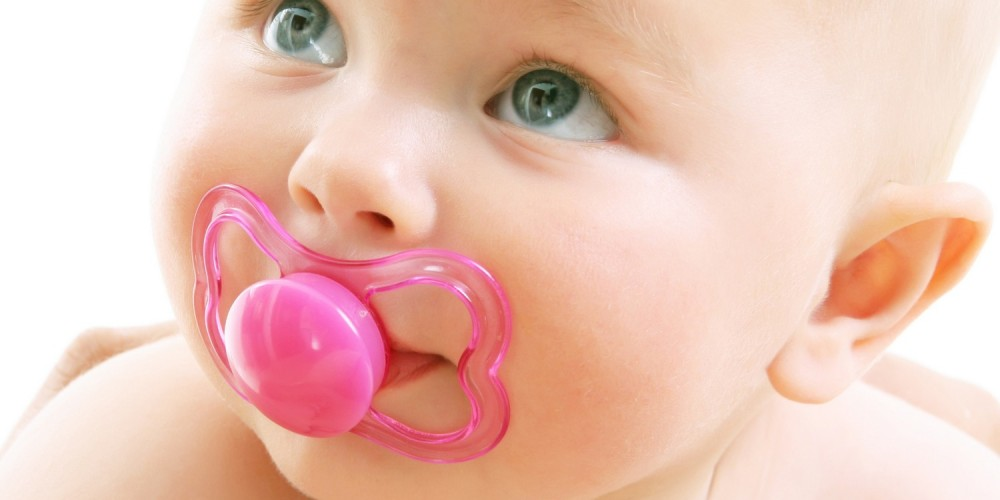 Baby mit pinkem Schnuller im Mund