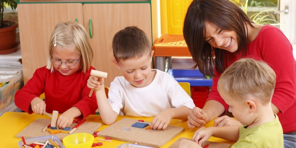Erzieherin und Kinder haben Freude am gemeinsamen Handwerken