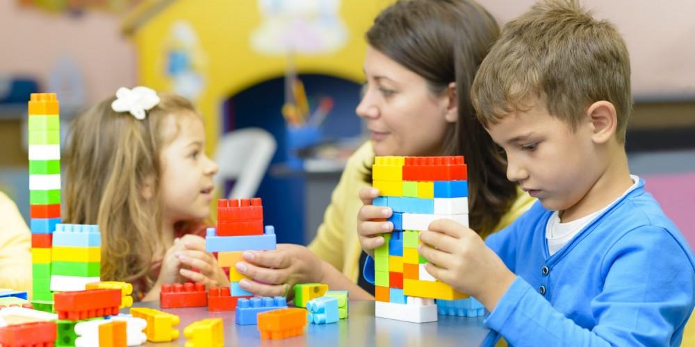 Kinder spielen mit bunten Bausteinen