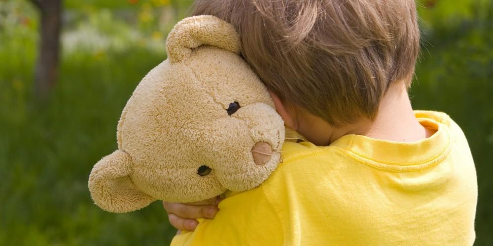 Kleiner Junge mit Teddybär im Arm
