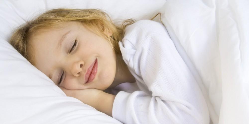 Kleines Mädchen liegt lächelnd im Bett und schläft