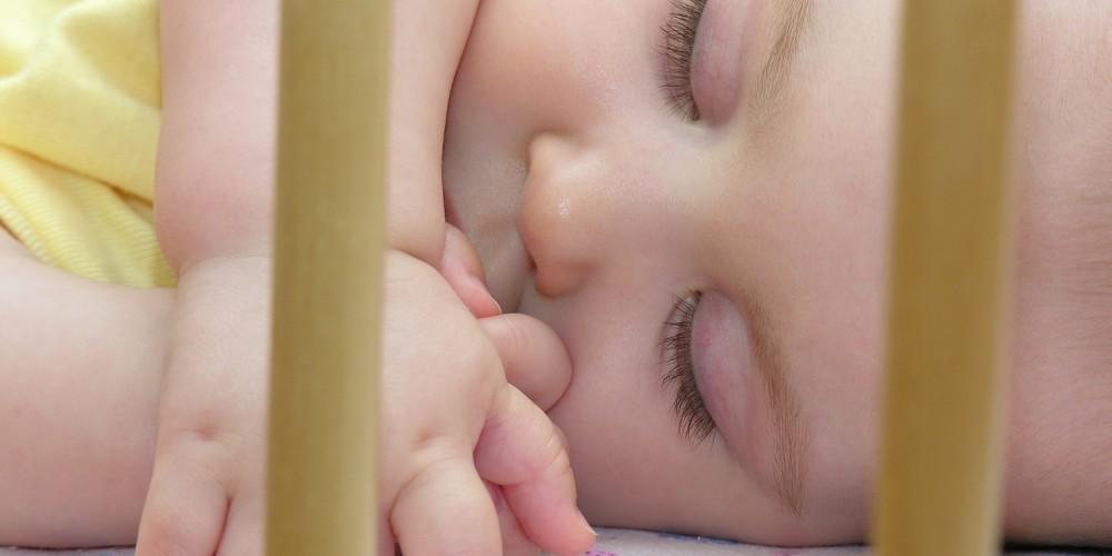 Schlafendes Baby im Gitterbett