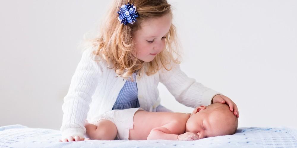 Kleines Mädchen streichelt ein schlafendes Neugeborenes
