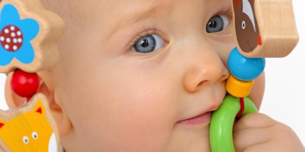 Baby spielt mit einer bunten Holzspielzeugkette