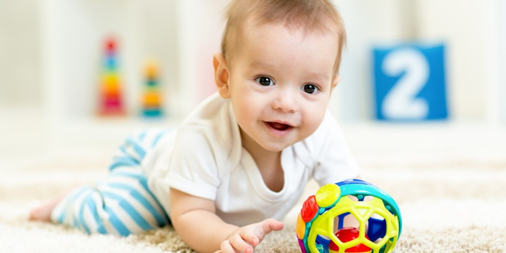 Kleinkind krabbelt hinter einem Spielzeug her