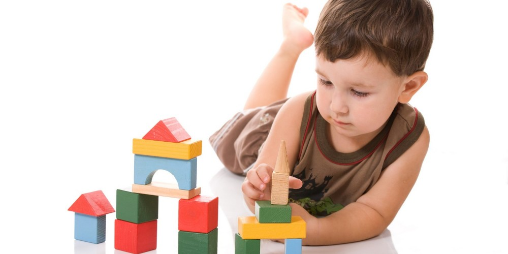 Junge beim Bauen mit Holzbauklötzen